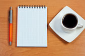Pen, notebook and cup coffee on table. View from above. — Stock Photo