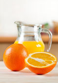 Oranges with a jug of juice — Stock Photo