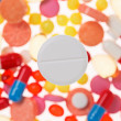 One big tablet (pill) macro view on blurred multicolored drugs b - Stock Photo