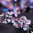 Diamond (small purple jewel) stones heap over black silk cloth b - Foto de Stock