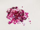 Diamond (ruby) stones heap over cream silk cloth background — Stok fotoğraf