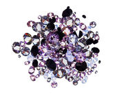 Many small purple diamond (jewel) stones heap isolated on white — Stock Photo