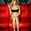 Bashful young blonde lady in black lingerie sitting on red leath - Stockfoto