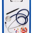 Blue medical clipboard with stethoscope and pills isolated on wh — Stock Photo #9696785