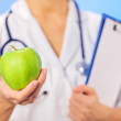 Doctor (woman) holding green apple with copy space on blue — Stock Photo