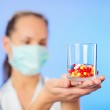 Pills, tablets and drugs heap in doctor's hand on blue backgroun — Stock Photo