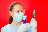 Doctor (woman) analyzing medical test tubes on red background — Stock Photo