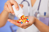 Pills, tablets and drugs pouring from bottle in doctor's hand on — Stock Photo