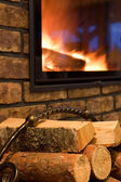 Fire wood against a fireplace — Stock Photo