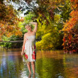 The girl with a bunch of flowers, standing in the river — Stock Photo
