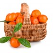 Ripe tangerines with leaves in basket — Stockfoto
