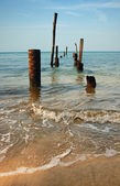 Old jetty pillars in sea — Stock Photo