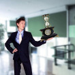 Businessman in office holding clock pyramid - Stock fotografie