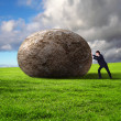 Businessman rolling a giant stone - Stockfoto