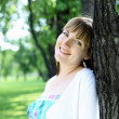 Стоковое фото: Young woman relaxing in the summer park
