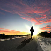 Man walking away at dawn along road — Stockfoto
