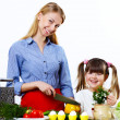 Young mother cooking at home with her daoghter - ストック写真