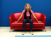 Young woman sitting on red sofa — Stockfoto