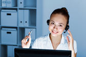 Young woman in business wear and headset — Stok fotoğraf
