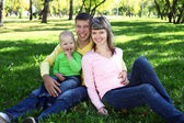 Young family with a child in summer park — Stock Photo
