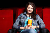 Young girl in cinema watching movie — Stock Photo