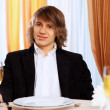 Young handsome man sitting in restaurant — Stock Photo #10128605