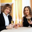 Couple in a restaurant with shampagne - Stock Photo