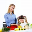 Young mother cooking at home with her daoghter — Stock Photo #10129270
