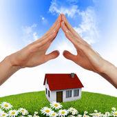 家と青い空を背景に人間の手 — ストック写真