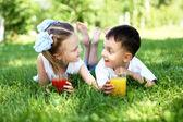 Lilla bror och syster i sommaren park — Stockfoto
