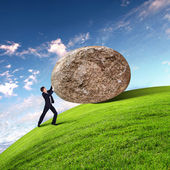 Businessman rolling a giant stone — Stockfoto