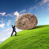 Geschäftsmann, einen riesigen stein rollend — Stockfoto