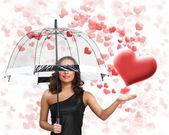 Jolie jeune femme avec parapluie et coeurs — Photo