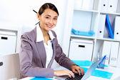Mujer joven en ropa de negocios trabajando en oficina — Foto de Stock