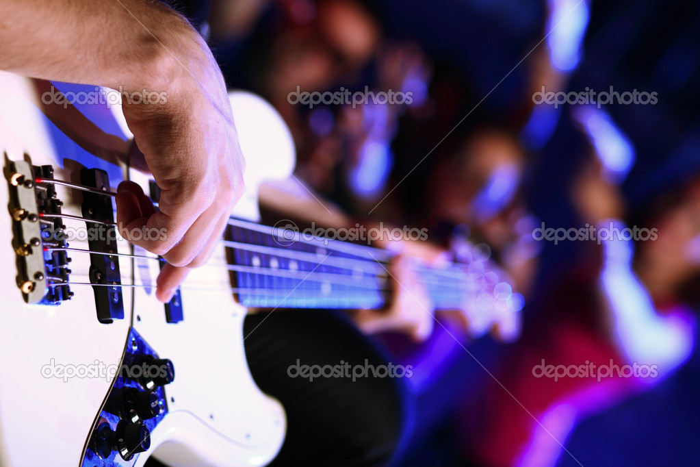 Young guitar player with instrument performing in night club  Stock Photo #10128726
