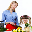 Young mother cooking at home with her daoghter — Stock Photo #10260089