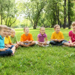 Group of children sitting together in the park - Stock Photo