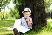 Porträtt av en pojke med en bok i parken — Stockfoto