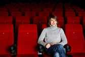Young man sitting in the cinema alone — Stock Photo