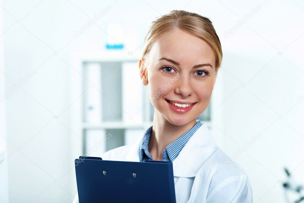 Young doctor in white uniform standing and holding papers  Stock Photo #10269690