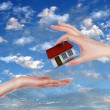 House and human hand against blue sky — Stok fotoğraf