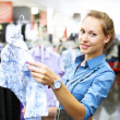 Woman in a shop buying clothes - Stock Photo