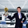 Businessman in office holding clock pyramid - Stock Photo