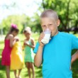 Stock Photo: Boy drinking milk in summer park