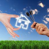 Ev ve mavi gökyüzü karşı insan eli — Stok fotoğraf