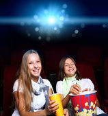 Two young girls in cinema — Stock Photo