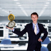 Businessman in office holding clock pyramid — Stock Photo