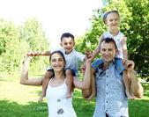 Rodzina z dwójką dzieci w parku lato — Zdjęcie stockowe