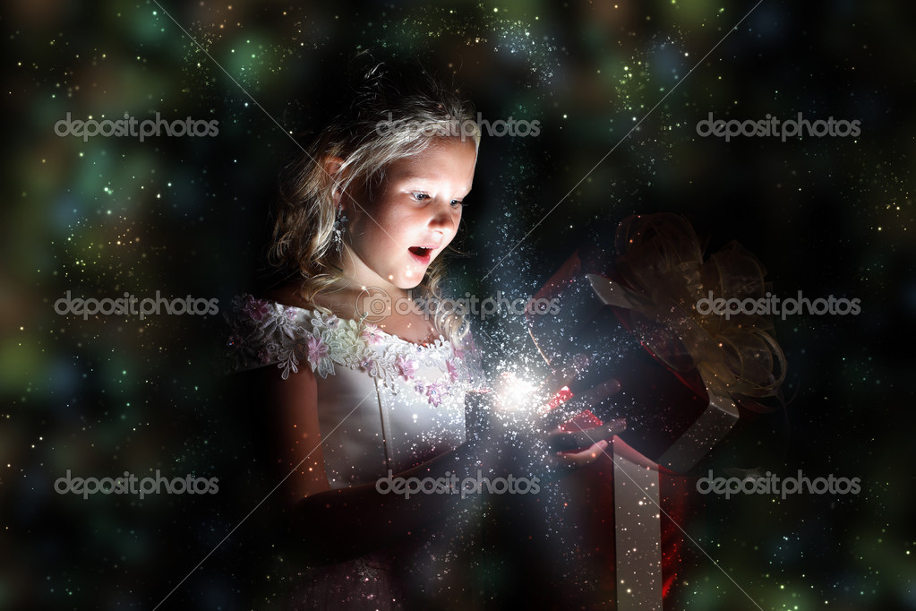 Child opening a magic gift box with lights and shining around — Stock Photo #10272542