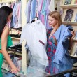 Girl seller helps shoppers — Stock Photo #7972941